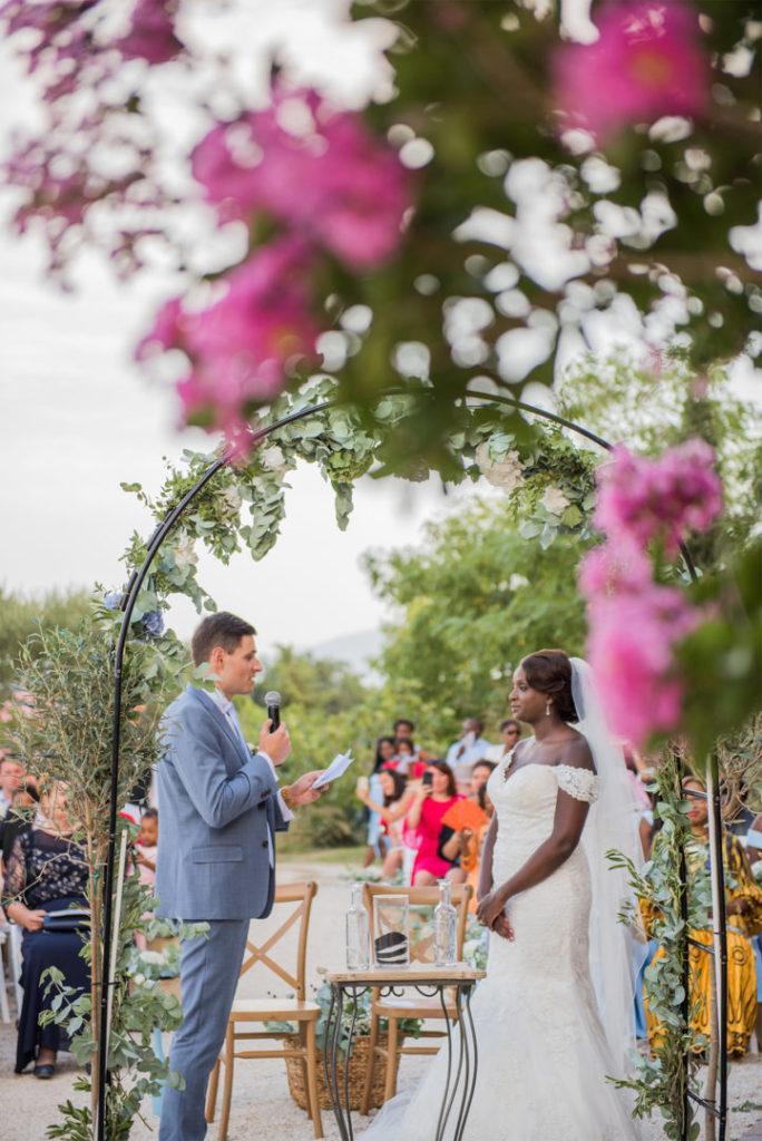 Discorus des mariés au travers de l'arche fleurie imaginée par By Maj, wedding planner et wedding designer à Perpinan et dans le 66 pour la cérémonie Laïque d'un mariage en extérieur sur le thème champêtre et pastel